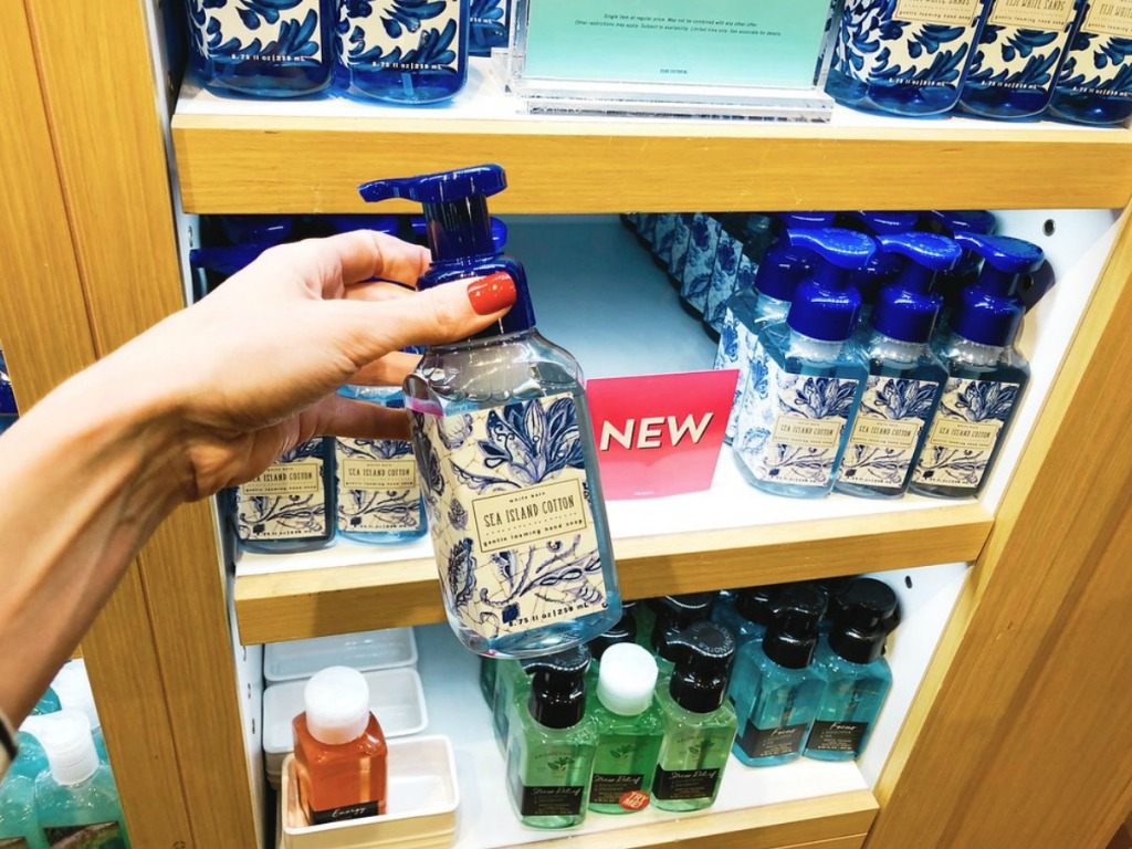 hand holding sea island cotton hand soap with soaps in the background on shelf