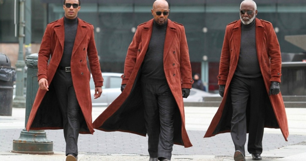 three actors from the movie shaft walking in orange trenchcoats