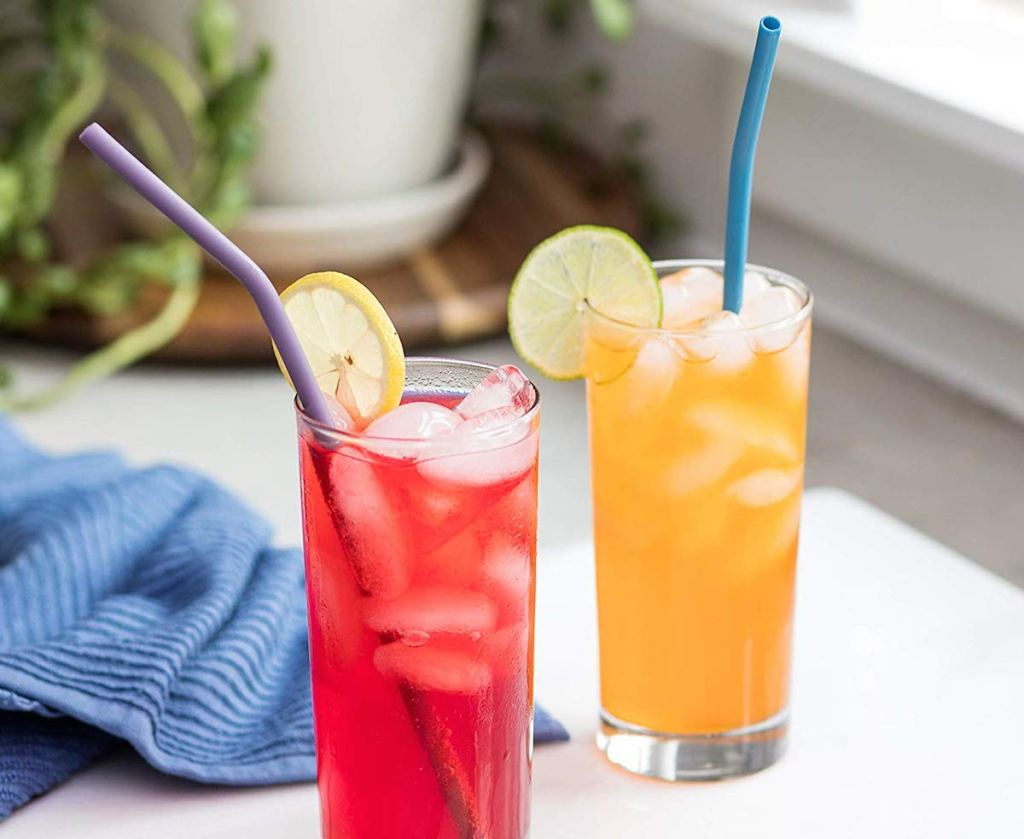 two glasses with red and orange iced drinks and straws