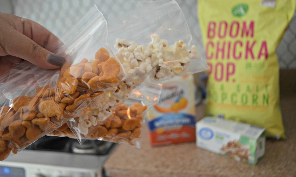 hand holding bags of goldfish and popcorn