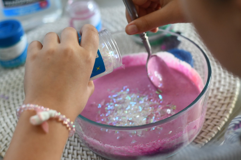 sprinkling glitter flakes into pink slime