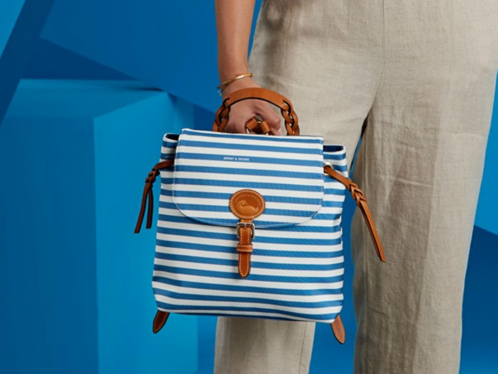woman holding striped blue backpack