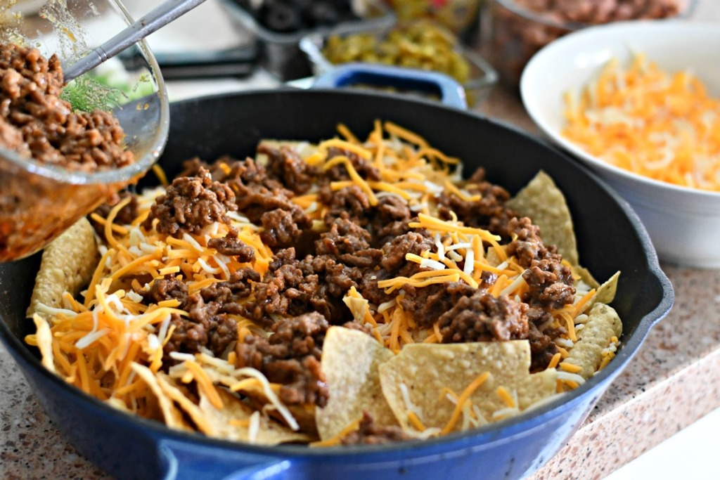 taco meat on top of skillet nachos