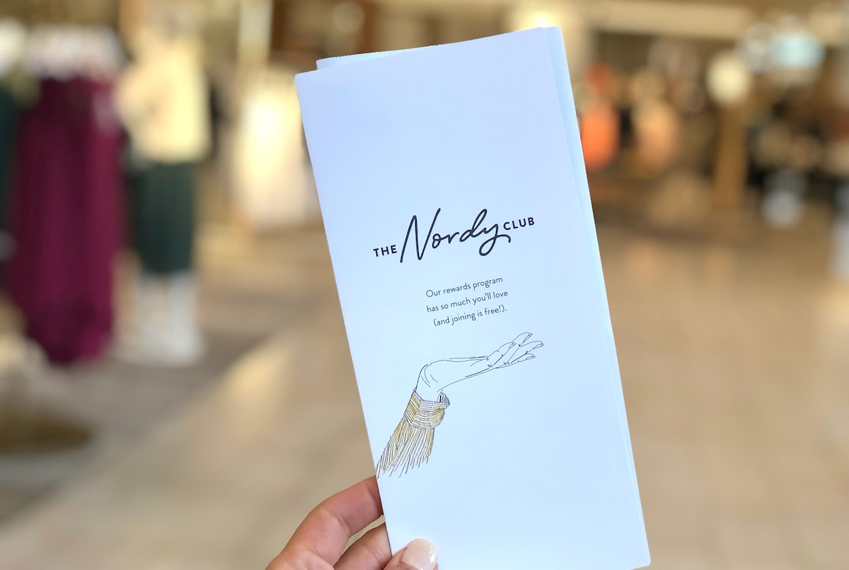 hand holding nordy club packet during nordstrom anniversary sale