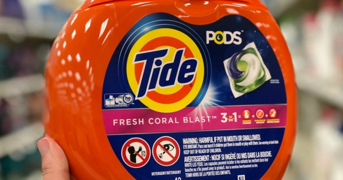 hand holding tide pods fresh coral blast w/ blurred background
