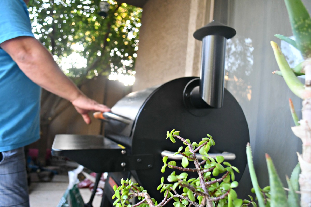 opening the lid of the Traeger smoker in backyard