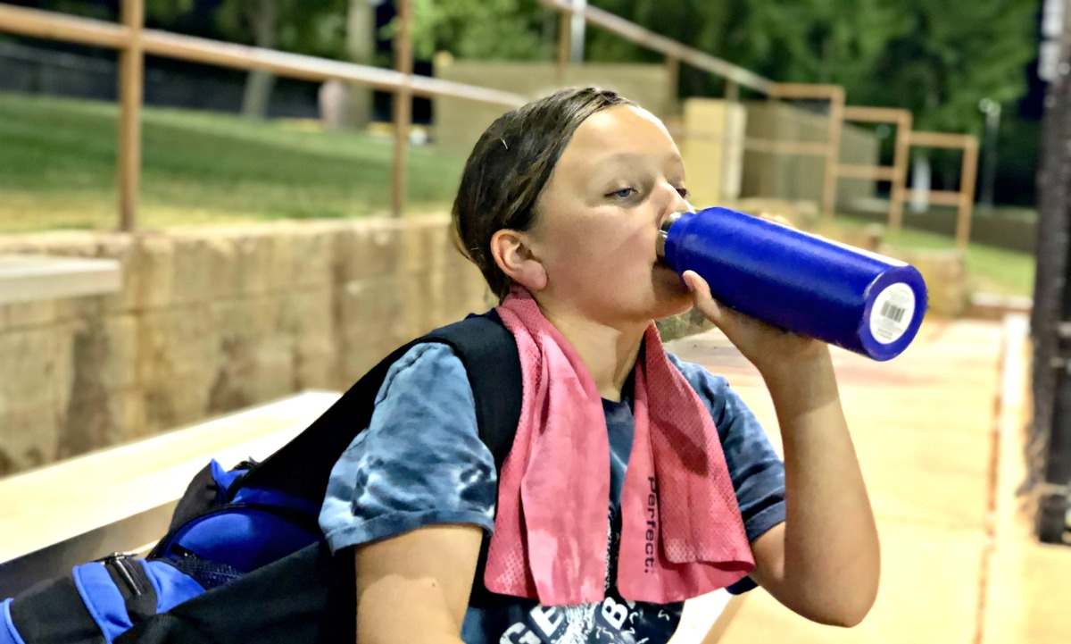 girl drinking water and using a cooling towel