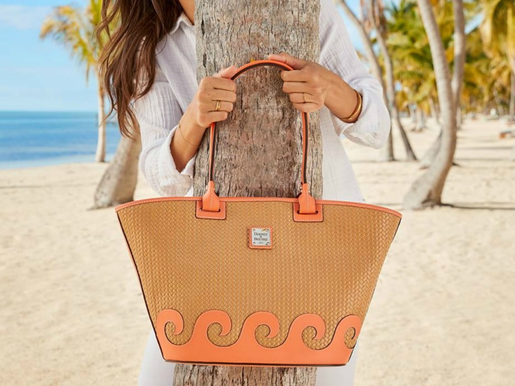 woman on beach by tree holding tote bag