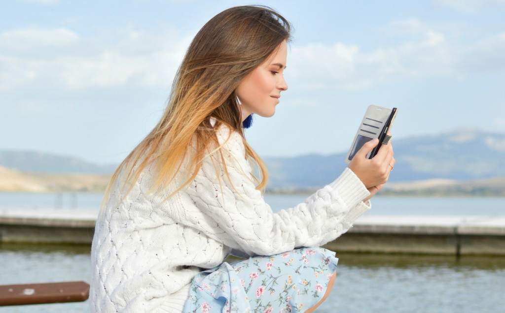 woman reading book on smartphone
