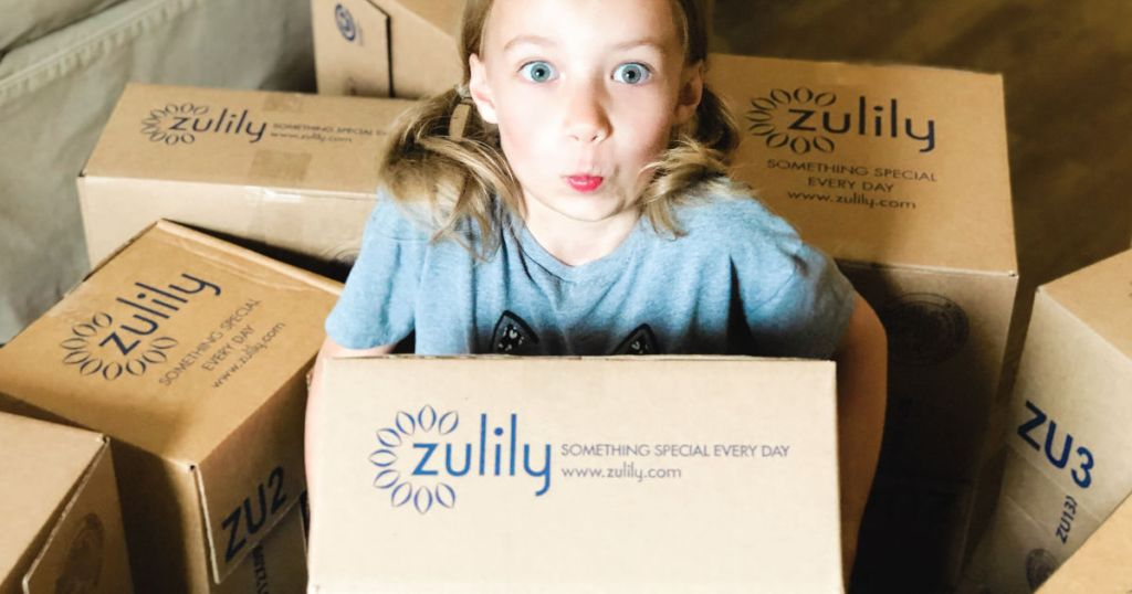 young girl with zulily boxes all around her holding one in living room