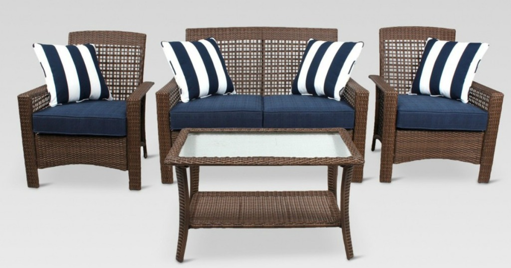 wicker patio set with navy cushions and striped pillows
