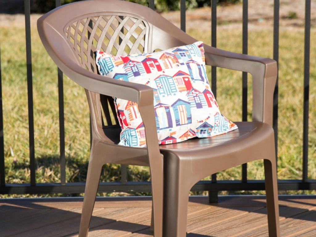 plastic chair on patio with pillow on it
