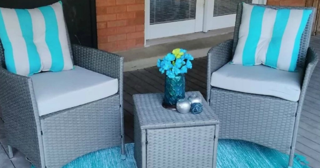 2 gray chirs with small table outside on porch
