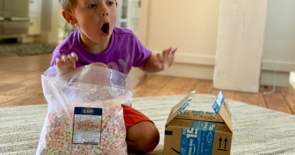 little boy holding cereal marshmallow bits bag and Amazon Prime box