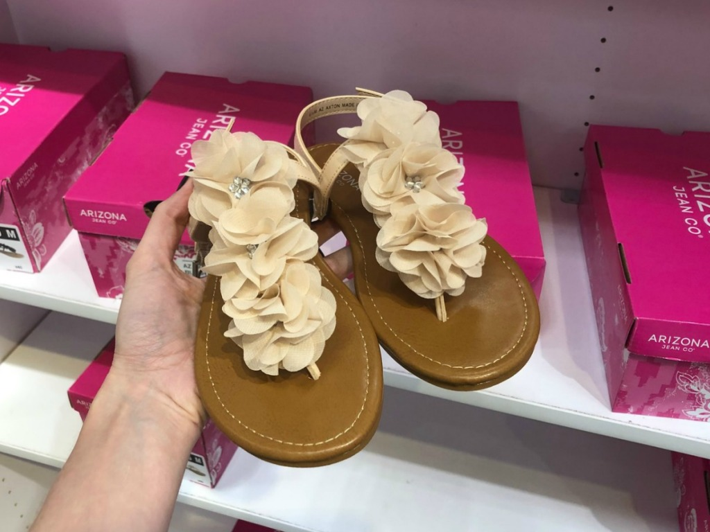 Arizona Axton Sandals held in front of shoe boxes