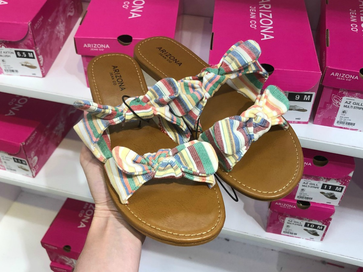 Arizona Gill Sandals held up in front of shoe boxes
