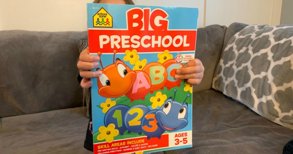 girl on couch holding the BIG Preschool book