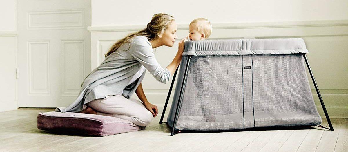 woman watching child in crib