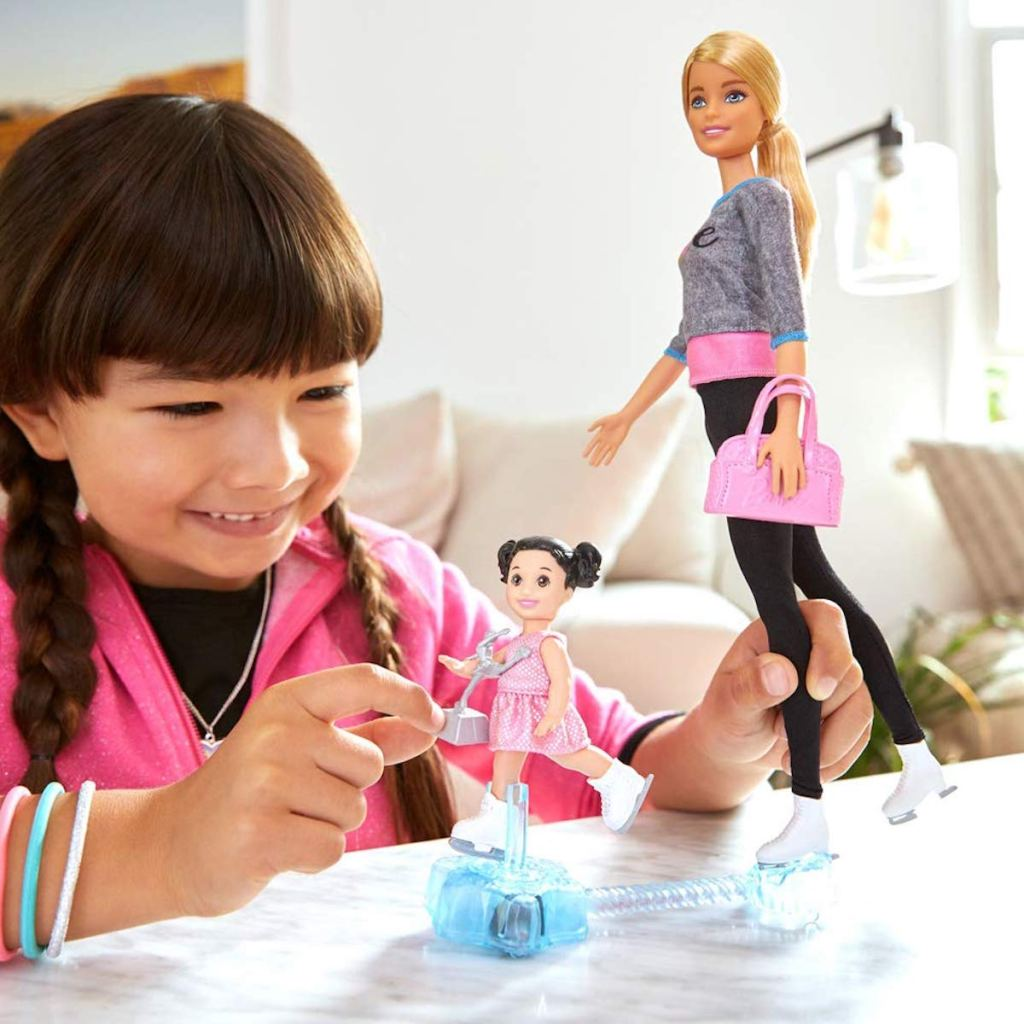 girl playing with Barbie Ice Skating Coach Doll & Playset