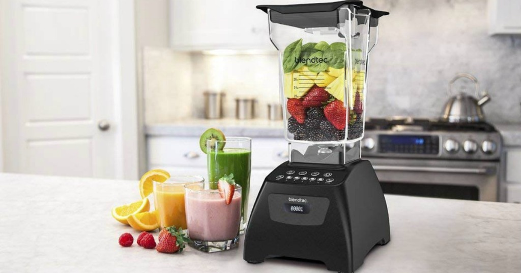 Black Blendtec-brand blender on a counter top filled with fruits and vegetables, with prepared smoothies nearby