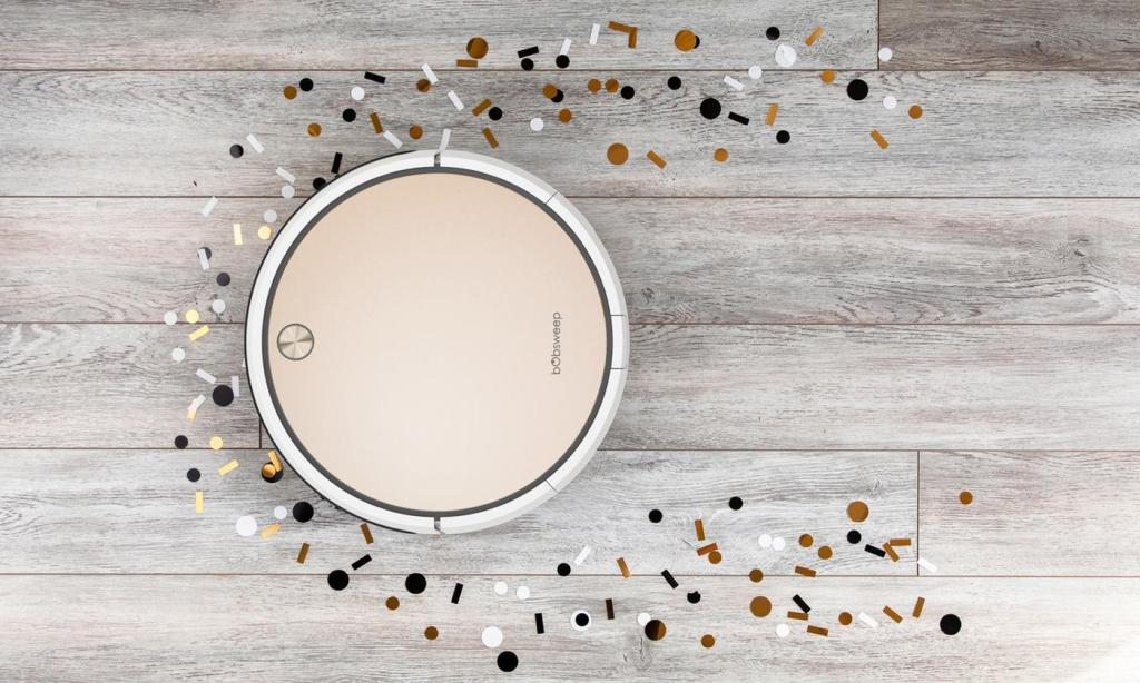 gold bobsweep pro robotic vacuum being used on hardware floor