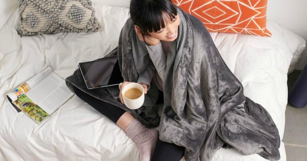 vrouw gewikkeld in deken drinken koffie