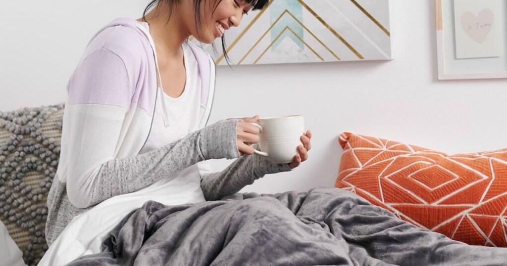 vrouw zittend op bed koffie drinken