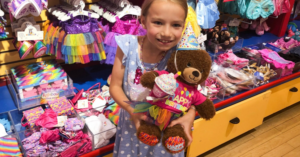 Girl holding Birthay Treat Bear inside Build-A-Bear Workshop
