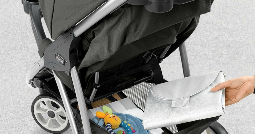 woman putting items into bottom backet of baby stroller