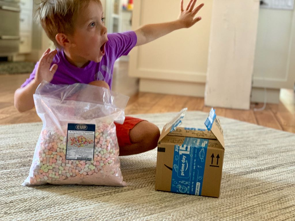 little boy with big bag of marshallow bits and Amazon Prime box