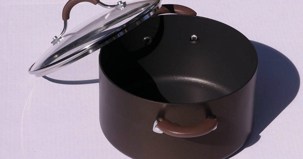 brown dutch oven with glass lid leaning on pot and purple background