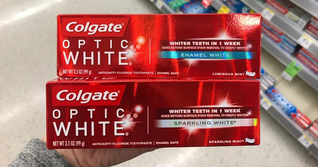 woman holding 2 boxes of colgate optic white toothpaste at store