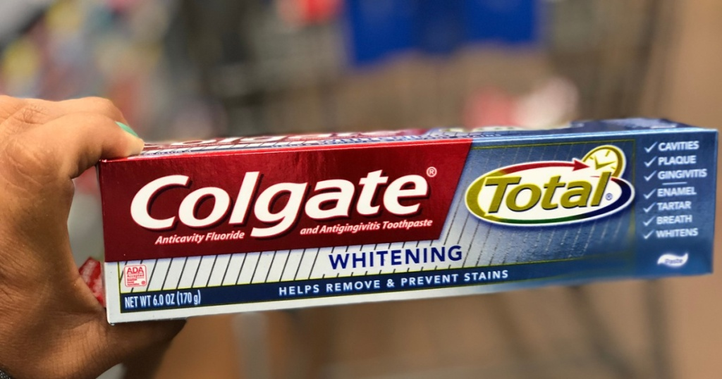woman holding colgate total toothpaste at store