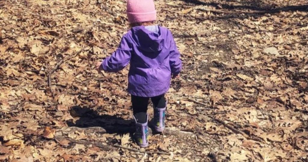 toddler walking through leaves wearing Columbia Rain Jacket