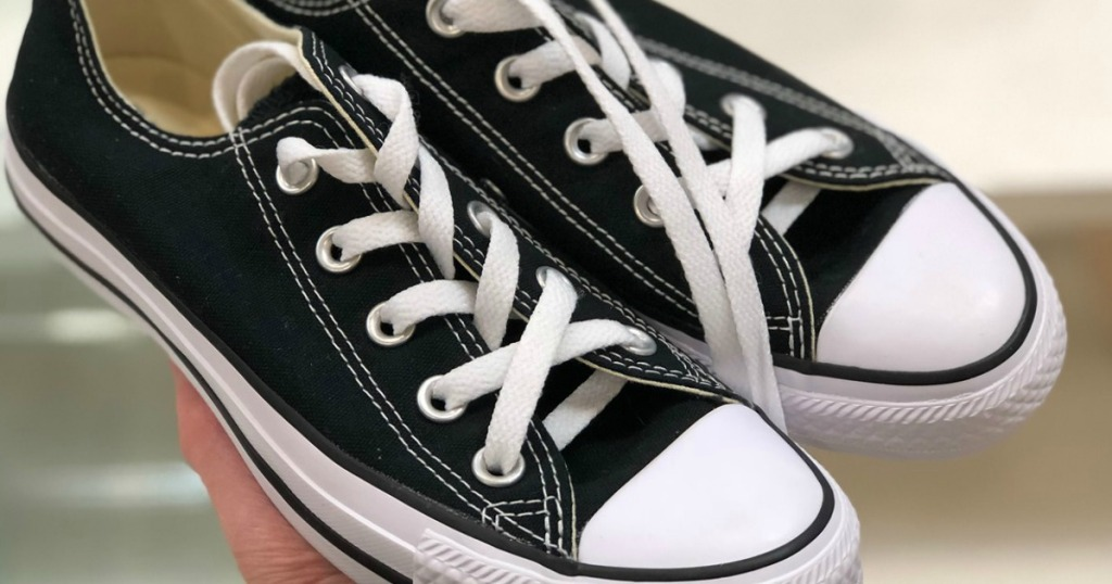 Converse All Star black shoes held in hand