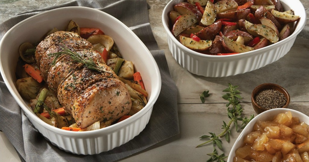 Set of bakeware from Corningware with a pork roast and sides on a wooden counter top