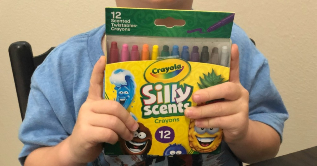 kid holding silly scents crayons