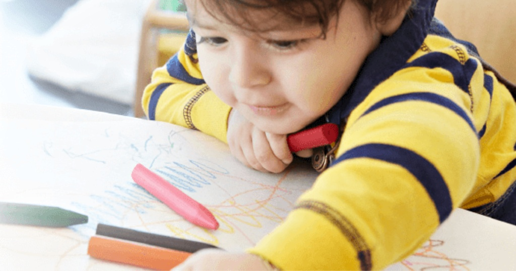 little boy coloring with crayons