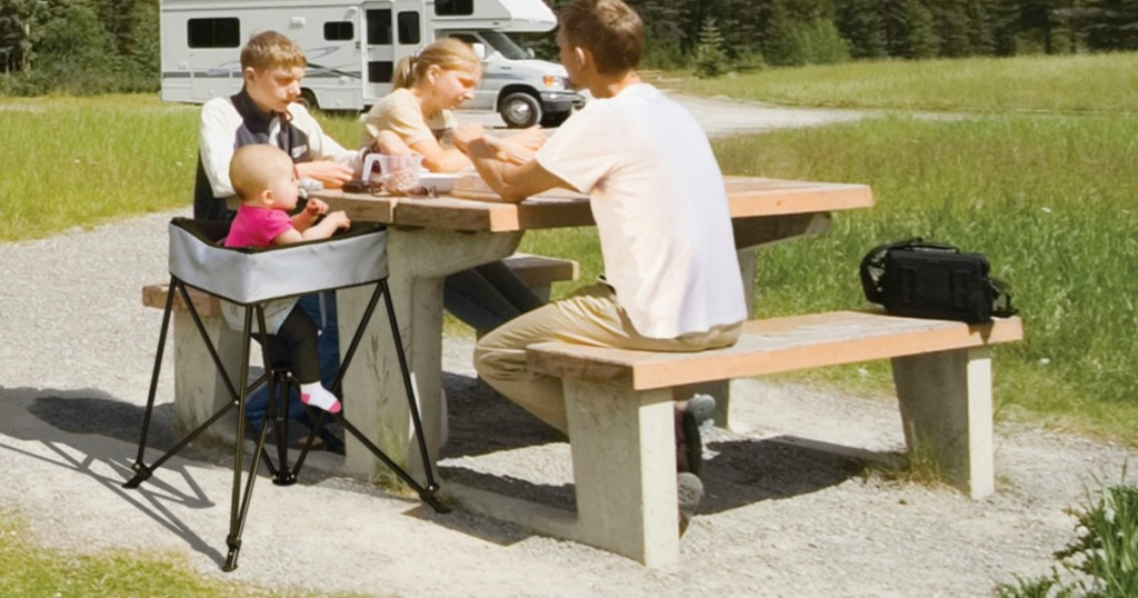 family sitting at campsite with baby in portable dining chair