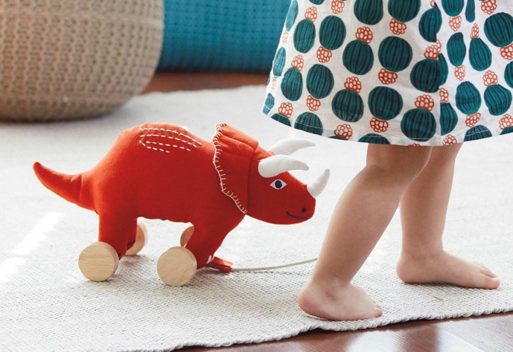 toddler girl walking rhino pull toy through living room