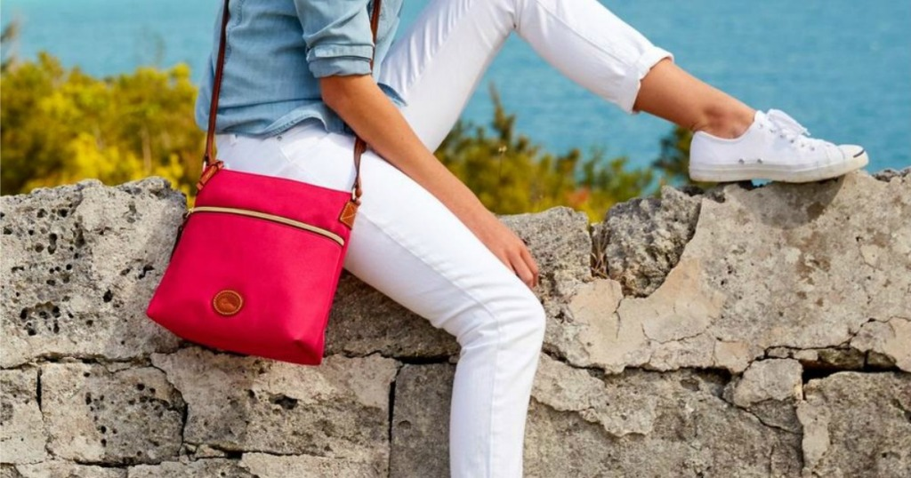 Woman sitting on rock wall with Dooney & Bourke Bag