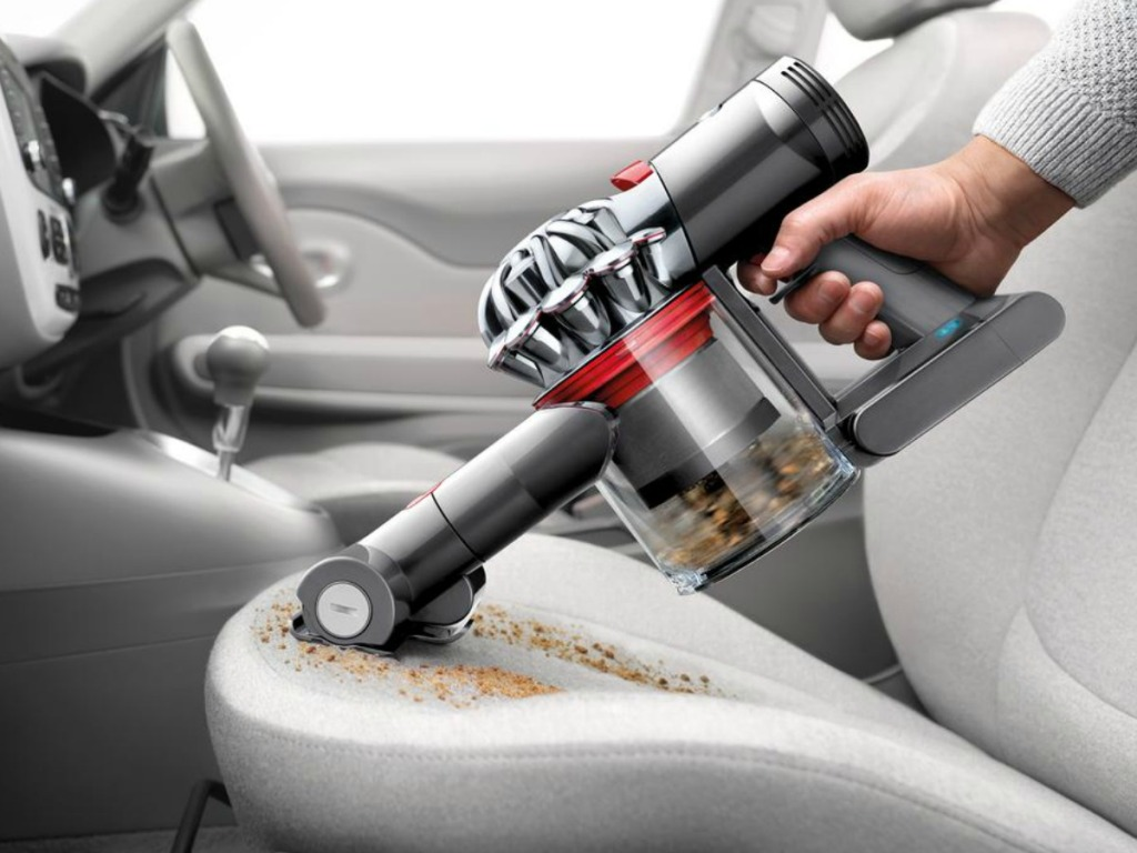 Dyson V7 Motorhead Extra Cordless Stick Vacuum Cleaner cleaing crumbs from seat in car