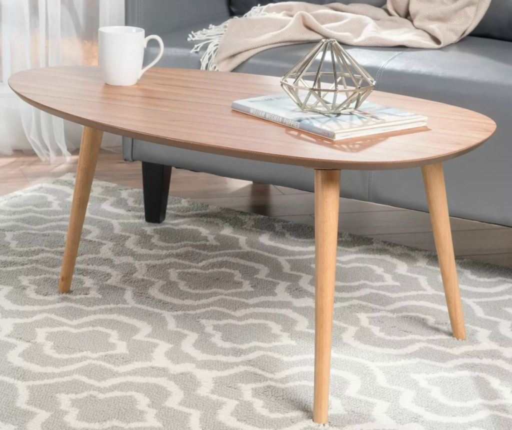Light wood coffee table in living room set-up with mug and accents