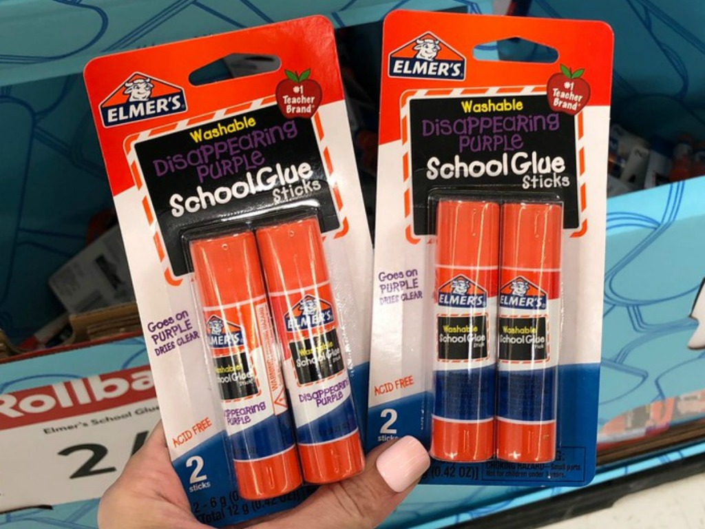 hand holding packages of glue sticks by store display
