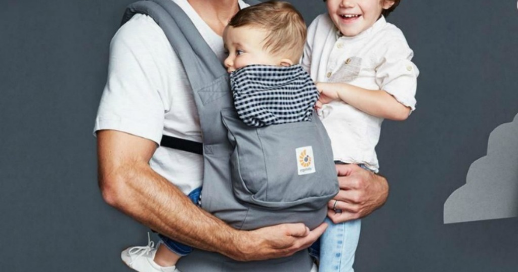 Baby being worn by dad in a gray and plaid baby carrier