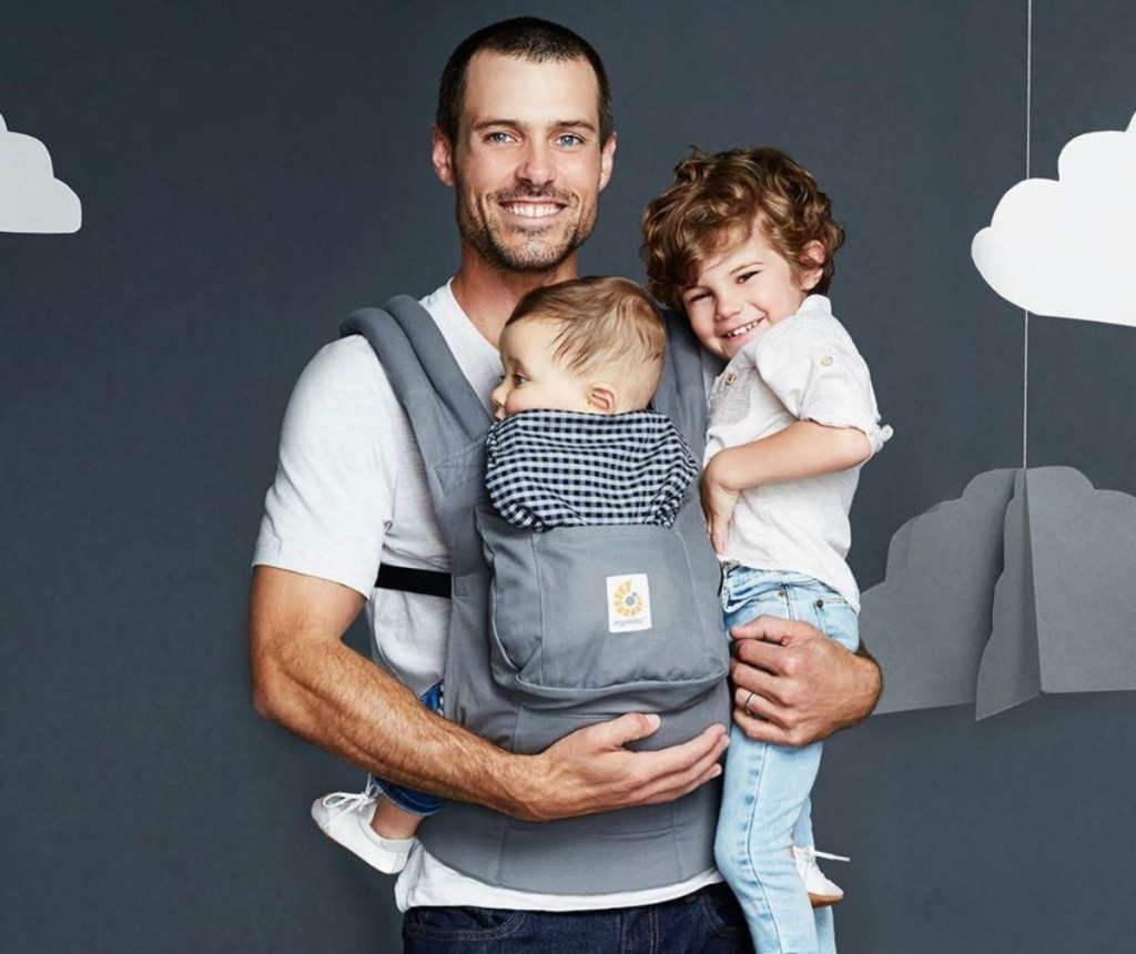 Father wearing baby in a carrier while holding toddler with a gray background