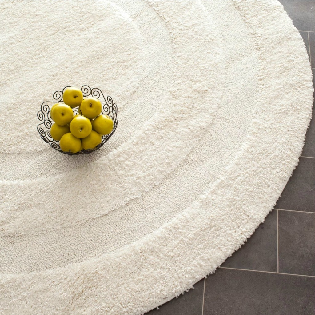 Creme-colored rug on dark floor with a bowl of golden apples