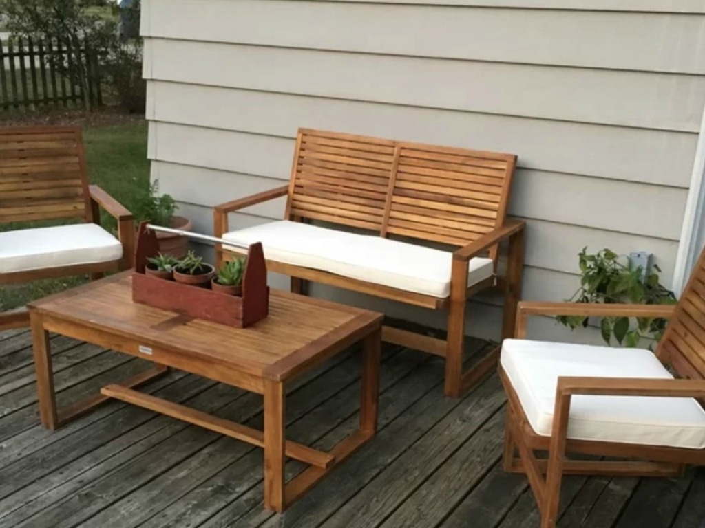 porch with table and chairs with cushions on it