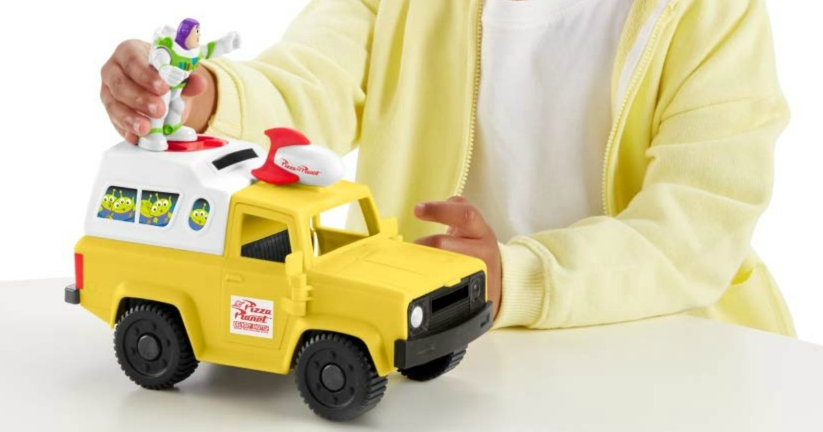 child holding Buzz Lightyear on top of toy Pizza Planet truck