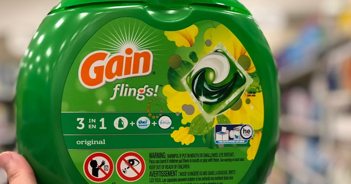 hand holding a container of gain flings laundry detergent